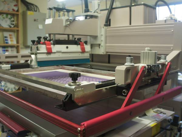 A machine is producing screen printing ceramic decals.