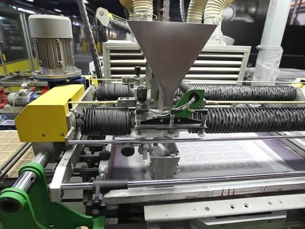 A machine is screen printing ceramic tiles.