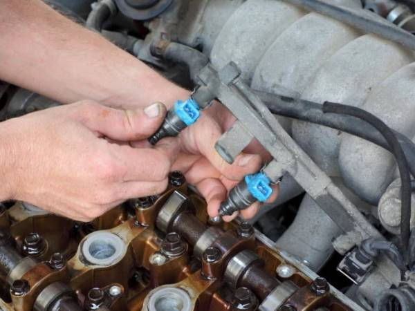A man is inspecting the injector of car.