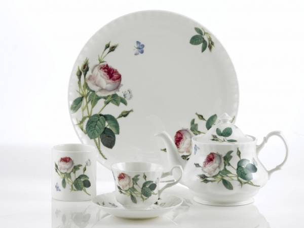 A dish, two cup and teapot with screen printed flower pattern on the table.