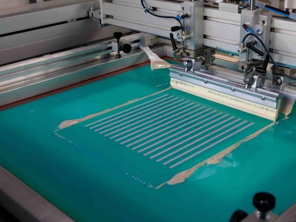 A machine is screen printing dye-sensitized solar cell.